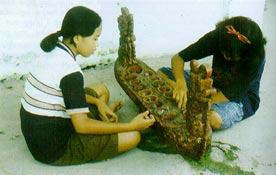Girls playing on an elaborate congklak playing board